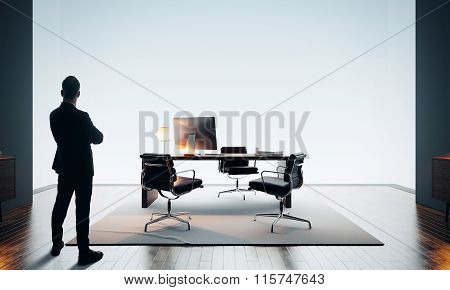 Businessman stands in modern office and looking at horizon. Color