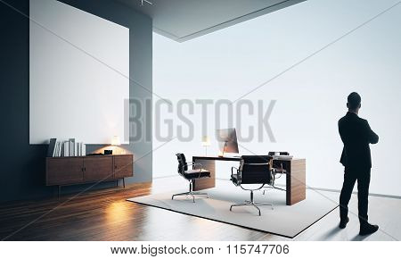 Businessman stands in modern office with one empty canvas. Color