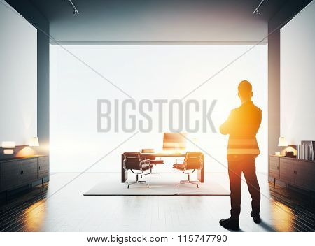 Businessman stands in modern office with two empty canvas. Bokeh effects