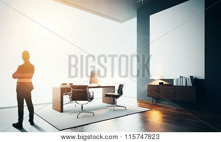 Businessman stands in modern office with one empty canvas. Bokeh effects