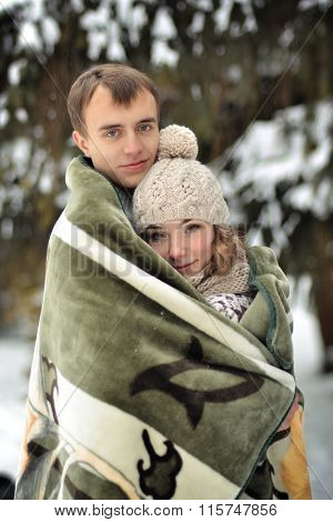 Enamored, happy, bonding, smiling, beautiful, nice, young, sweet couple wrapped in warm, new blanket