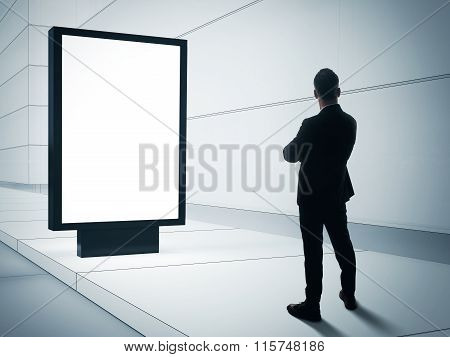 Business man looking at blank lightbox on the empty street.