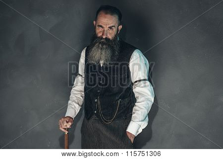Vintage Bearded Man In 1900 Style Fashion With Cane Against Grey Wall.
