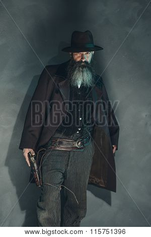 Vintage Crook With Long Beard Holding Gun In 1900 Style Clothing Against Grey Wall.