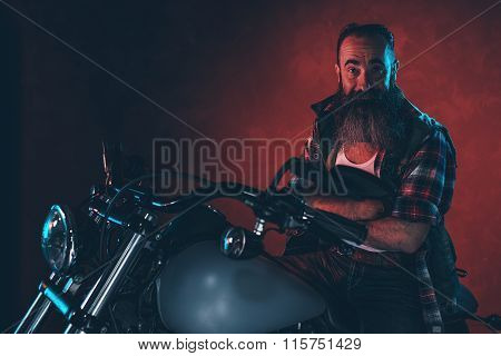 Cool Man With Long Gray Beard On Motorcycle At Night.