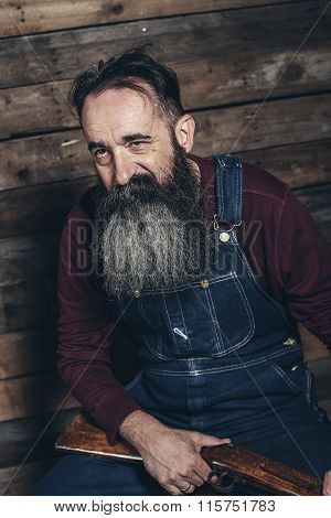 Vintage Farmer Holding Rifle Sitting On Wooden Crate In Barn.