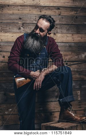 Vintage Farmer Holding Rifle Standing Against Wooden Wall In Barn.
