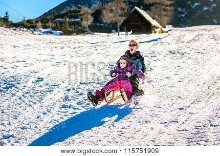 Mother And Little Child Are Sledging Very Fast In Ski Mountain Resort