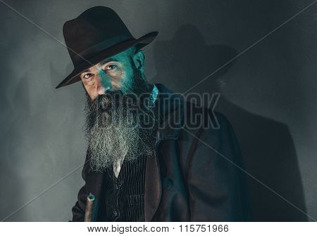 Spooky Vintage Bearded Man With Rifle In 1900 Style Fashion Against Grey Wall.