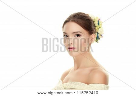 Closeup beauty portrait of young calm brunette woman with flower headpiece and bare shoulders lookin