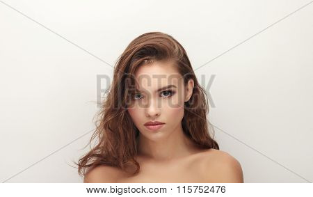 Closeup beauty portrait of cute grumpy brunette woman looking into camera on white studio background