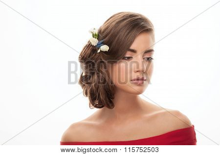 Young adorable brunette woman in red shirt with bare shoulders showing low bun hairstyle with flower