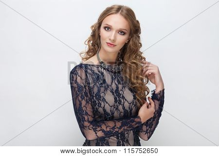 Young cute cheerful woman with curly hairstyle in blue dress posing on white studio background touch