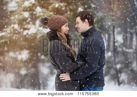Young couple in love in the winter forest