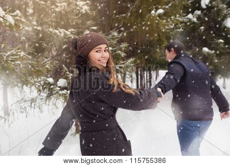 A loving couple walking in winter park. It's snowing, winter.