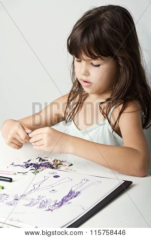 Little girl sharpens pencils