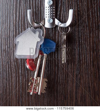 Key and House shaped keychain on wooden background