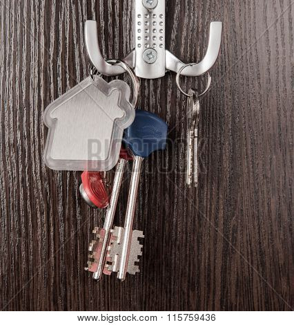 Keys And House Shaped Keychain On Wooden Background