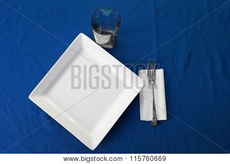 Fork silverware with white plate on blue background dinner setting