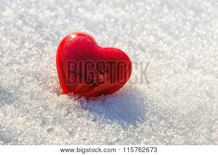 Red heart on ice wet snow selective focus
