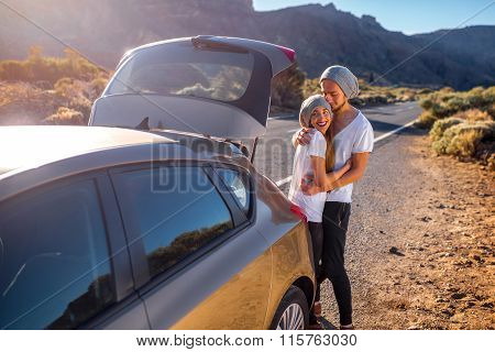 Young couple travelers having fun near the car