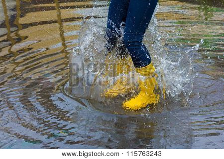 Girl With Rain Boots Jumps Into A Puddle