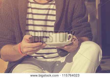 Hipster guy drinking coffee and using cellphone.Hipster guy drinking coffee and using cellphone.