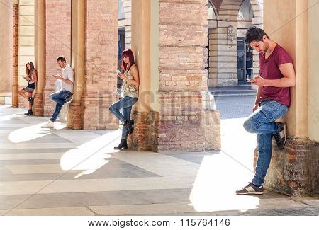 Group Of Young Fashion Friends Using Smartphone In Urban Old City Center - Technology Addiction