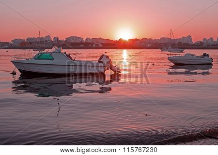 Motor yachts mooring in the harbor from Portimao in Portugal at sunset