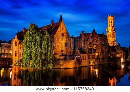 Famous view of Bruges-  Rozenhoedkaai with Belfry and old houses along canal with tree. Brugge, Belgium
