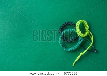 Three Simple Green Paracord Bracelets Placed On A Green Grainy Paper Surface