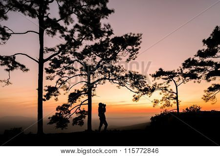 Silhouette of traveler is taking photograph on mountain with sunset view. Phukradung, Thailand.