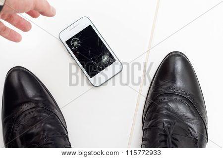 Businessman raises his broken smartphone from the floor