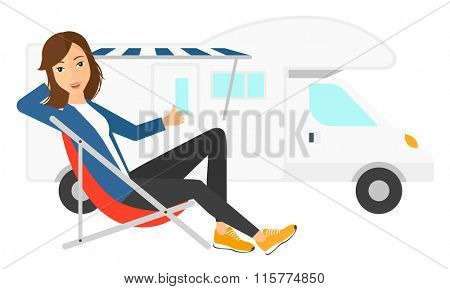Woman sitting in front of motorhome.