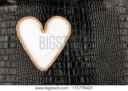 Symbolic Heart Made Of Rope Lying On A Crocodile Leather