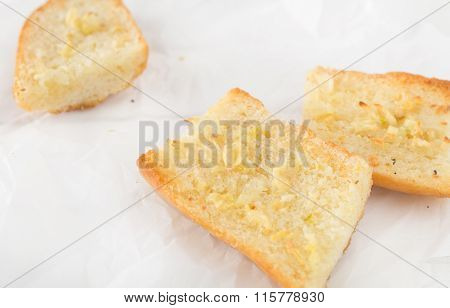 pieces of garlic bread made with baguette on white paper