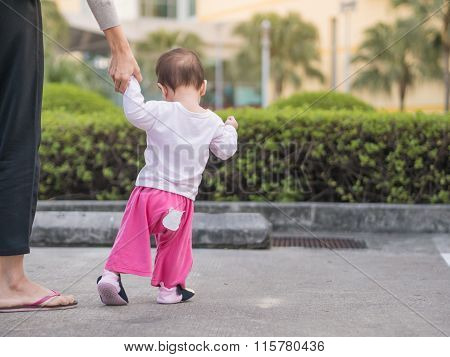 Asian Toddler Walking First Step In Park Morning. Mother Hold Baby Hand.