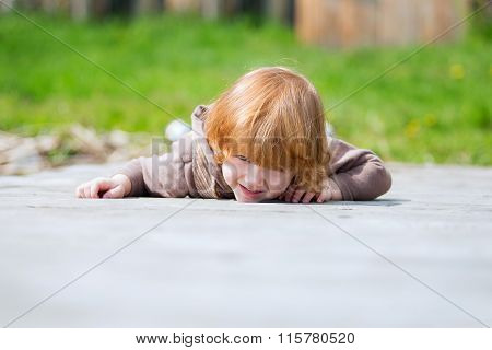 Red-haired girl lying on a wooden bridge