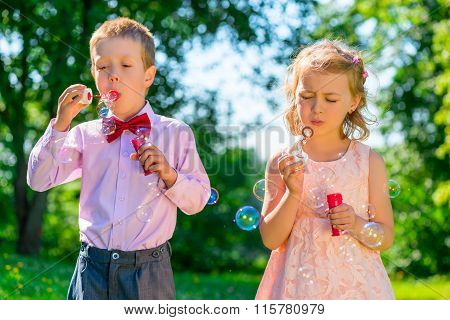 Portrait Child With Soap Bubbles On A Summer Day