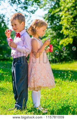 Vertical Shot Of Children 6 Years Of Age With Soap Bubbles On Nature