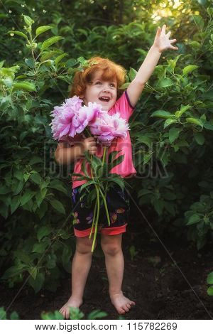 Little girl with a bouquet of peonies excitedly shouts