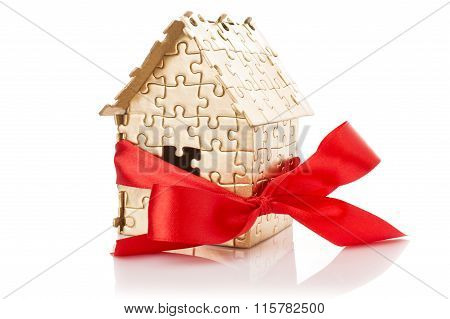 Real estate concept - Hand holding house architectural model with red bow on it isolated