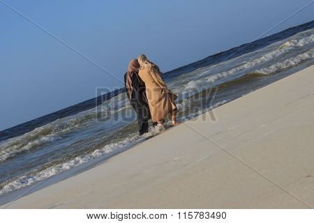 Unidentified Female Friends Walking Along Seashore In Muslim Traditional Dress