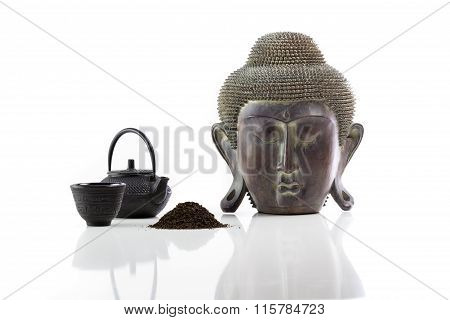 Buddha head, teapot, cup and tea on a white background