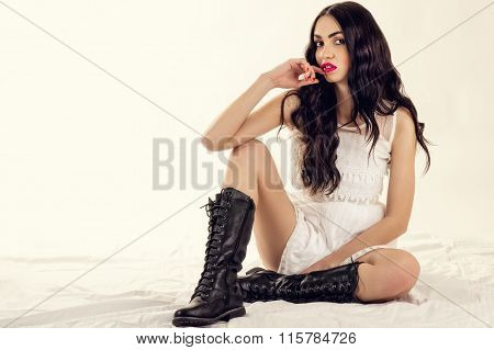 beautiful woman sitting on the floor in black boots