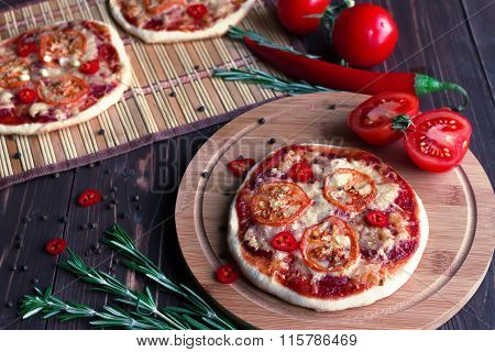 Mini pizza with tomatoes on a dark background