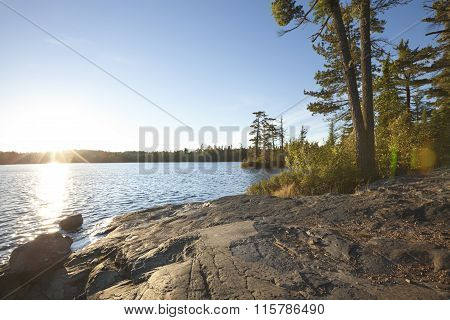 Sunset On Lake With Rocky Shore In Northern Minnesota