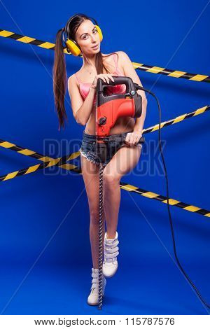 Sexy Brunette In Building Protective Headphones Shorts With Construction Tool Drill Hammer On A Blue