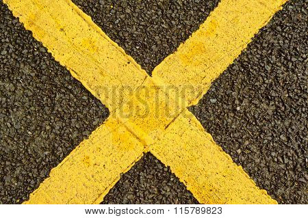 Yellow cross on the asphalt