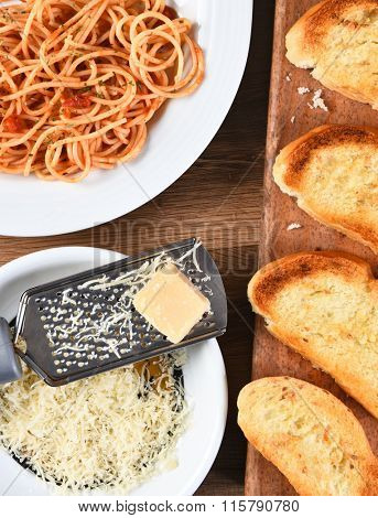 Overhead view of a cheese grater with parmesan cheese on a rustic wood kitchen table. A plate of spaghetti and garlic bread on board are also shown.